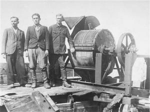 Члены зондеркоманды 1005 позируют на фоне костемольной машины в Яновском концлагере (июнь 1943 — октябрь 1943)